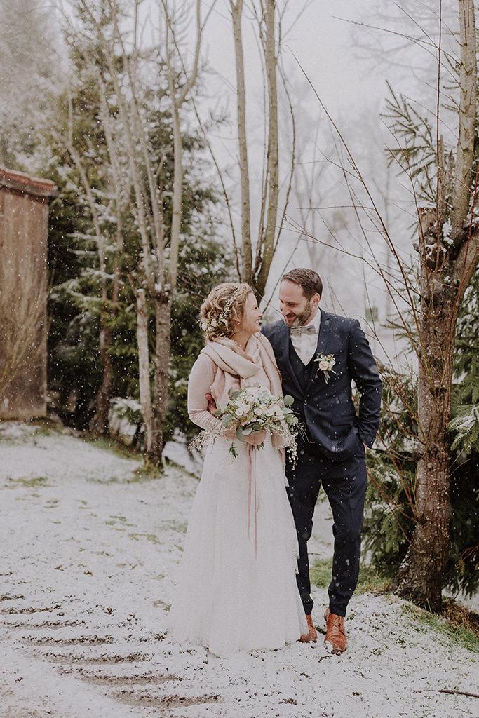 Brautpaar lächelt sich im gehen an