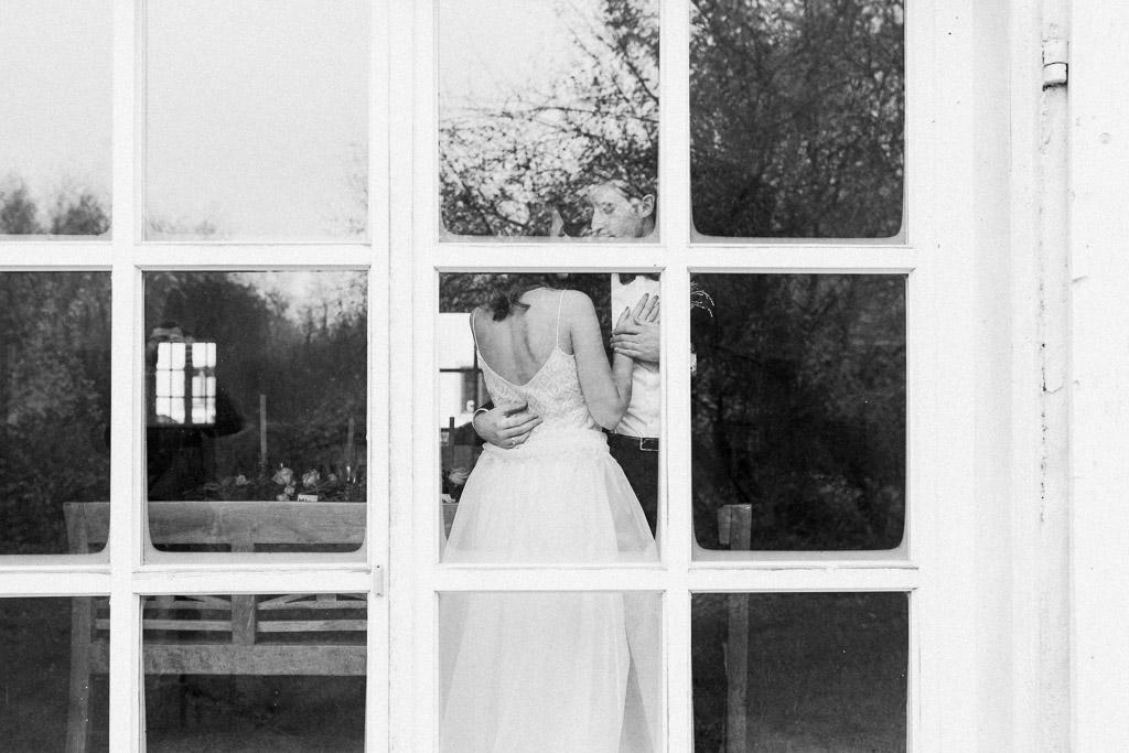 Brautpaar durch Fensterfront sichtbar
