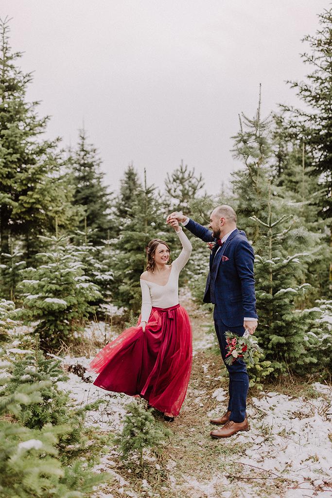 Tanzendes Brautpaar inmitten von Christbäumen
