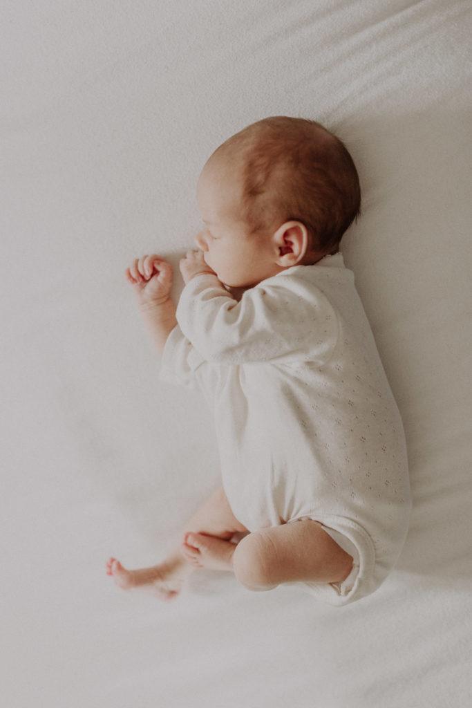 Newborn Helene schlafend ganz in weiß liegend auf dem Bett