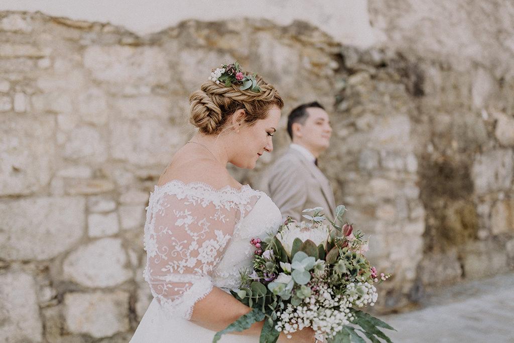 Braut im Fokus vor Steinmauer