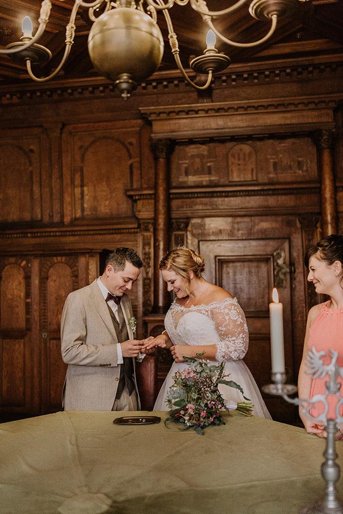 Bräutigam steckt seiner Frau den Ring an den Finger