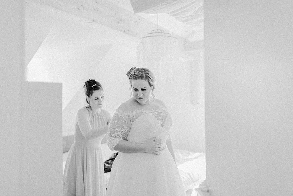 Der Braut wird geholfen ihr Brautkleid zu schließen