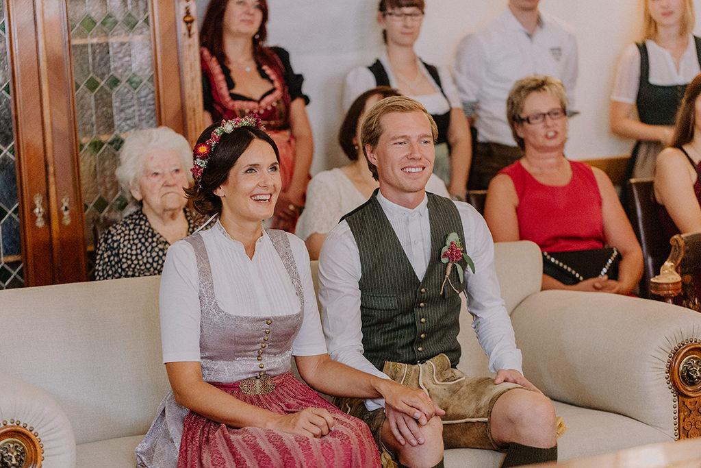 Das Brautpaar sitzt lachend auf der Couch während der Trauung im Standesamt in Landshut