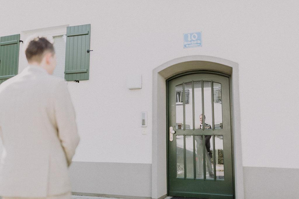 Der Bräutigam wartet vor der Haustüre auf seine Braut