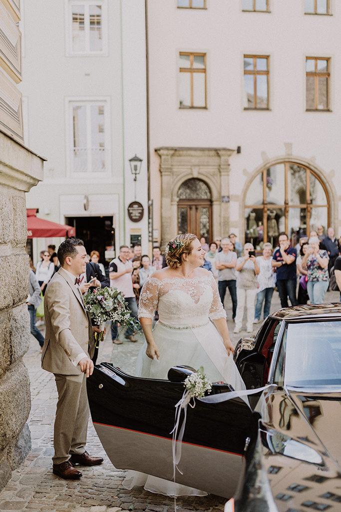 Braut und Bräutigam kommen aus dem Brautauto