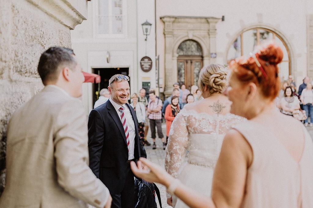 Hochzeitsgast lächelt das Brautpaar an