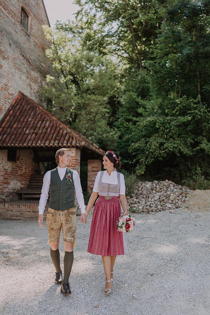 Das Brautpaar geht gemeinsam während dem Portrait Shooting auf der Burg Trausnitz