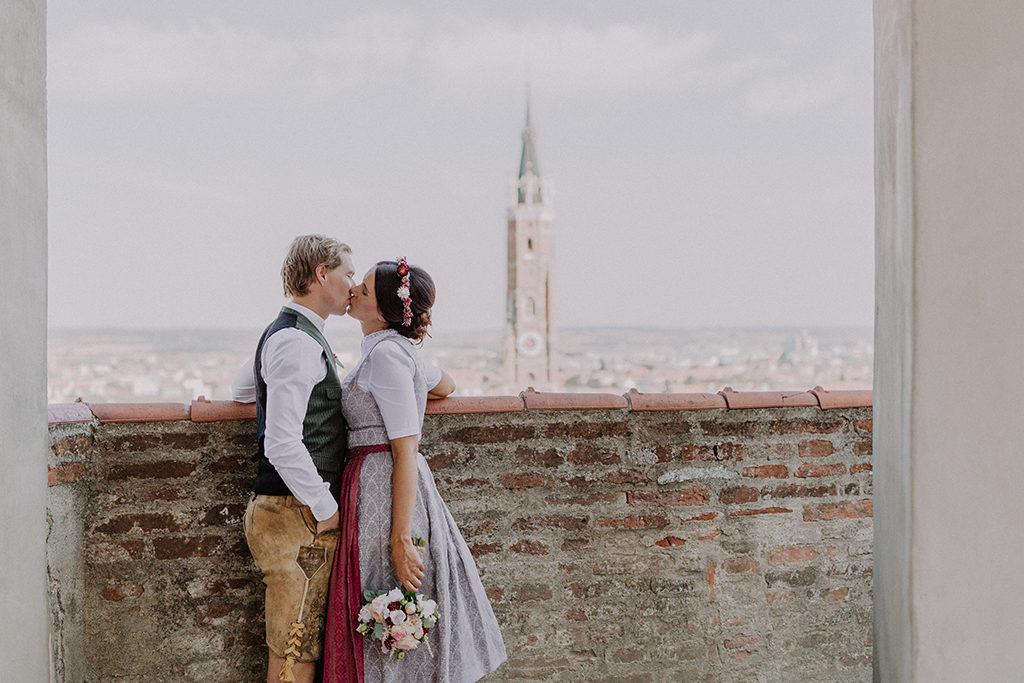 Brautpaar küsst sich vor der Kulisse der Stadt und der Martinskirche in Landshut auf der Burg Trausnitz