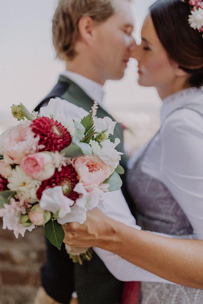 Fine Art Foto mit viel Schärfe und Unschärfe. Das Brautpaar ist im Hintergrund unscharf zu sehen und im Vordergrund ist der Strauß dargestellt.