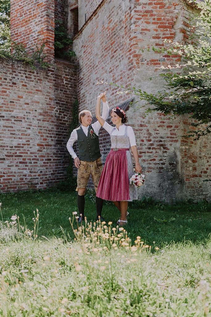 Das Brautpaar tanzt vor alten Steinmauer auf der Burg Trausnitz