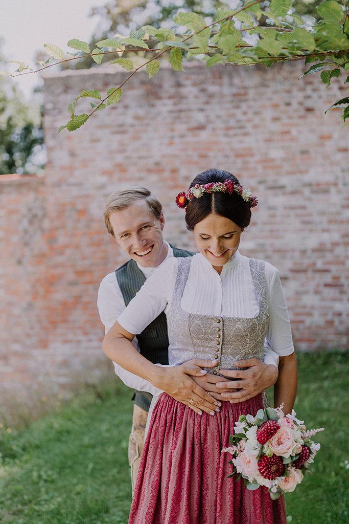 Brautpaar lachend während dem Portraitshooting vor Steinmauer