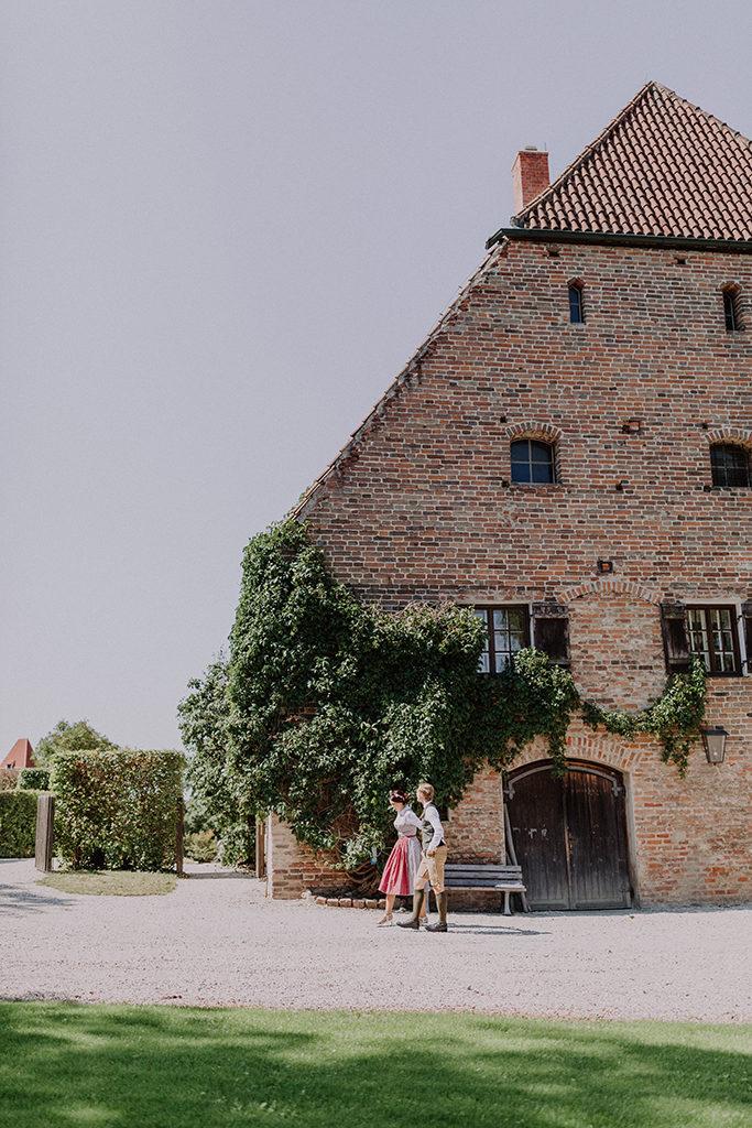 Brautpaar gemeinsam gehend vor altem Gutshaus