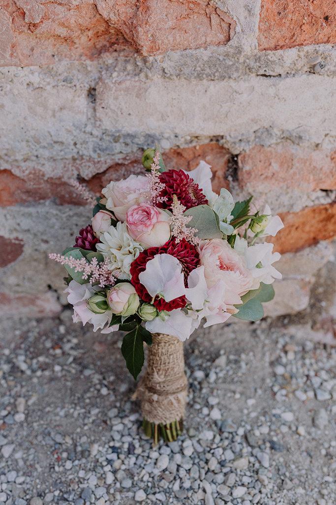 Foto des Brautstraußes vor roter Steinmauer
