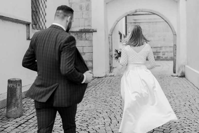 Brautpaar gehend von hinten mit schwingendem Rock in Deggendorf