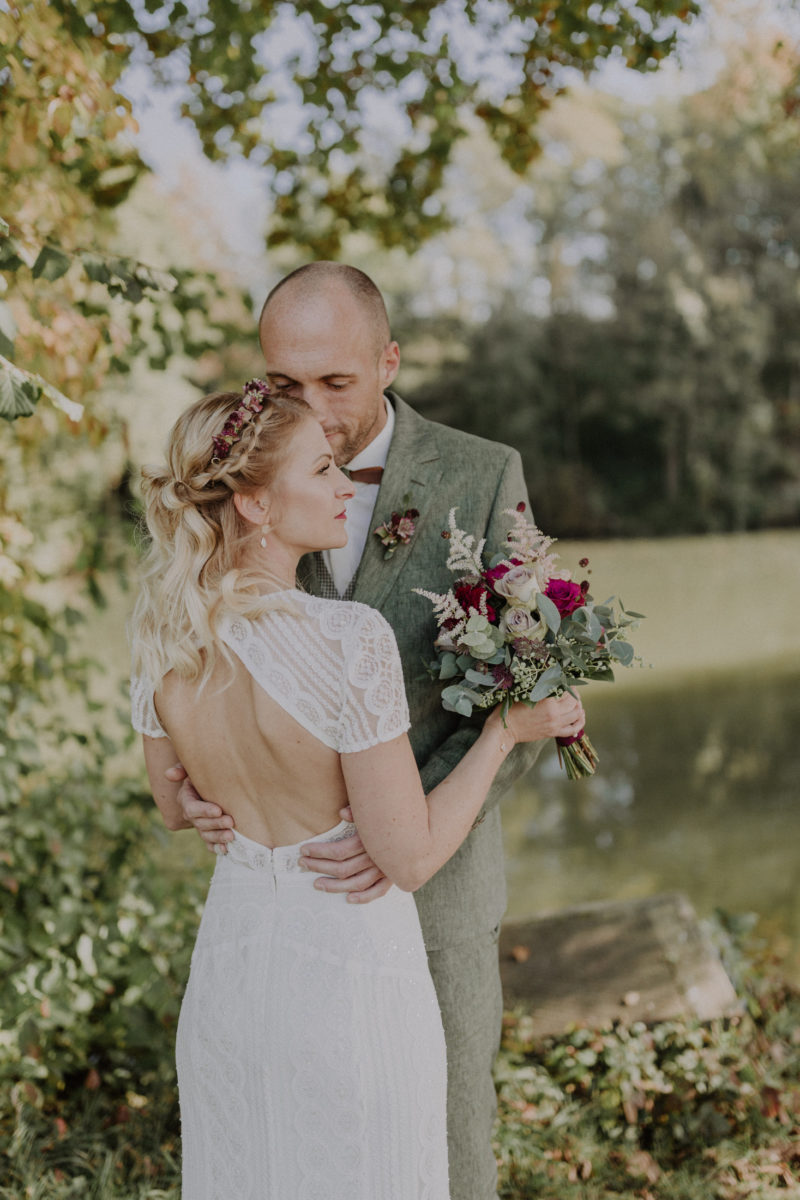 Brautpaar vor herbstlichen Kulisse eines Sees