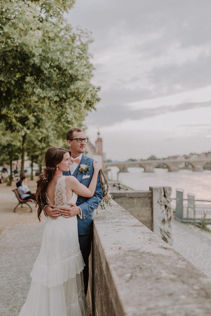 Brautpaar auf die Donau blickend.