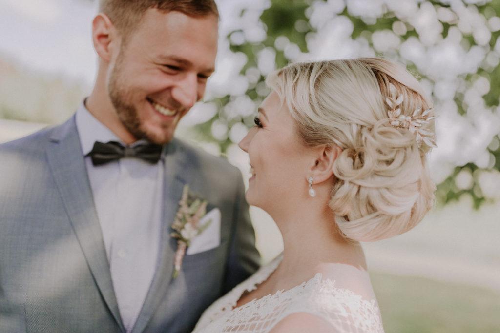 Brautpaar lacht sich herzlich an, der Schärfepunkt liegt auf dem Haar der Braut