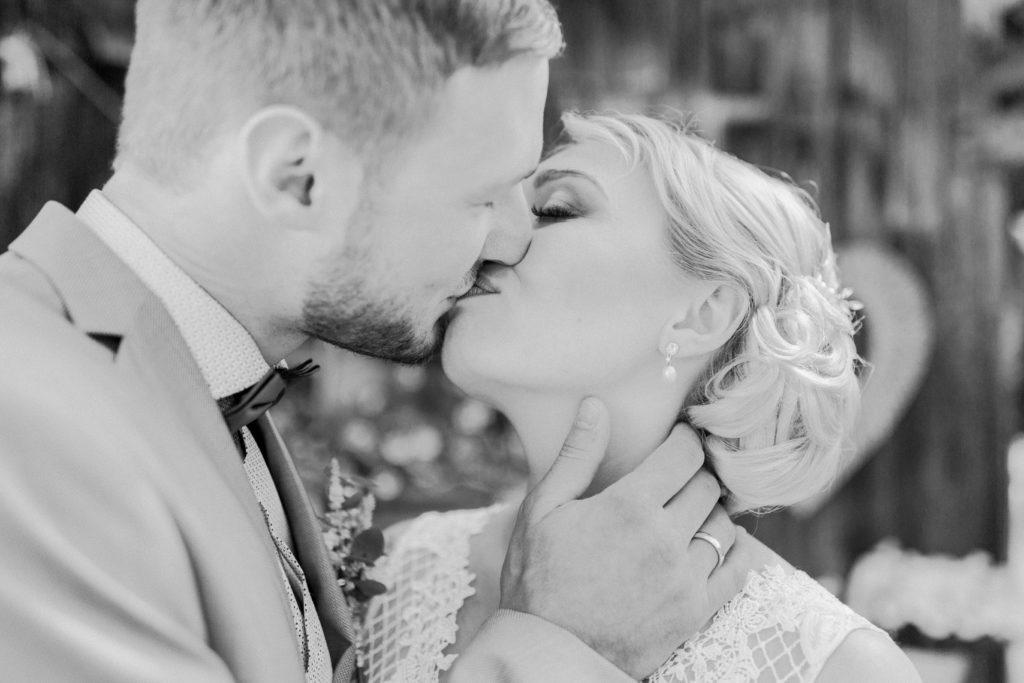 Schwarz-Weiß Foto von küssendem Brautpaar