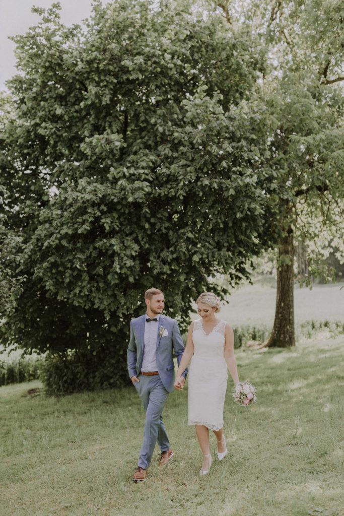 Brautpaar läuft eine Wiese entlang und Bräutigam sieht seine Braut an