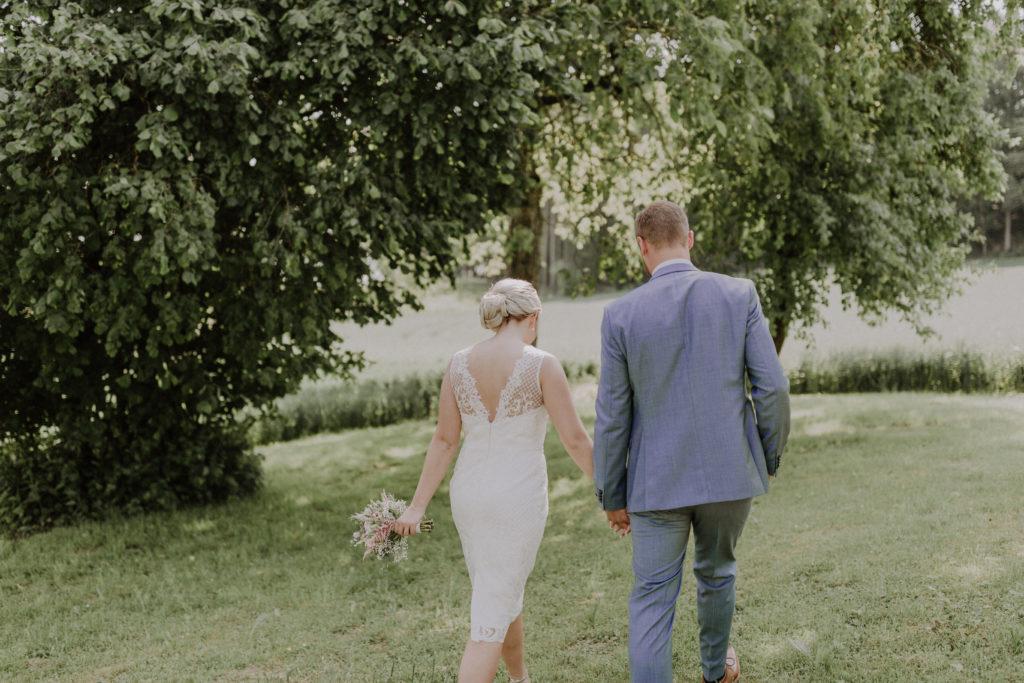Brautpaar läuft von der Kamera weg, man sieht die Rückenansicht der Beiden