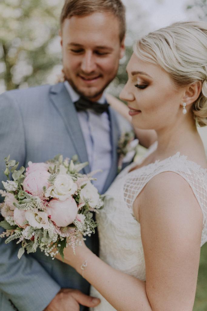 Brautpaar sieht den Brautstrauß an, der Fokus liegt auf dem Strauß, der Rest ist unscharf