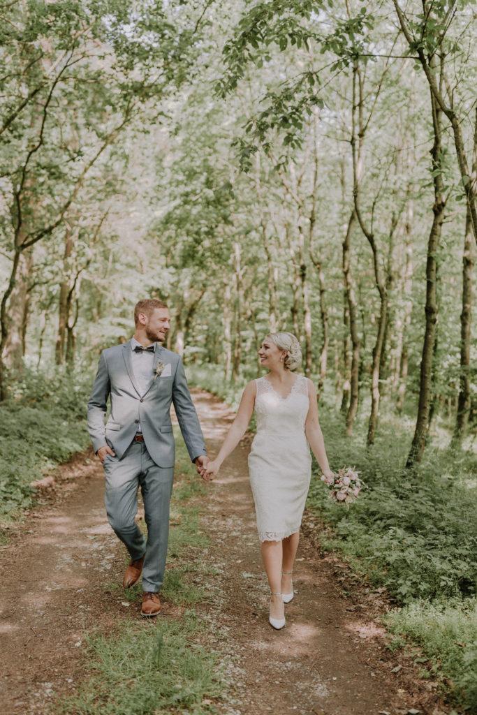 Brautpaar läuft in einer Waldlichtung den Weg entlang