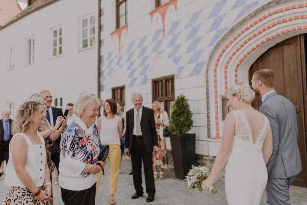 Gäste begrüßen das Brautpaar und freuen sich mit ihnen