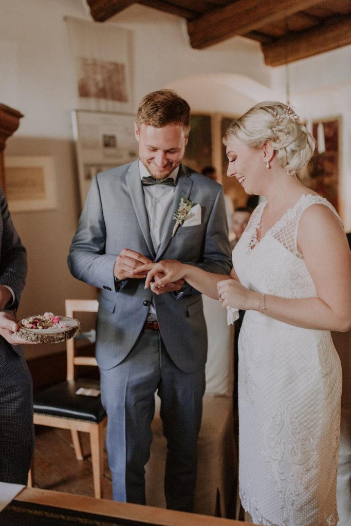 Bräutigam steckt seiner Braut den Ring an den Finger