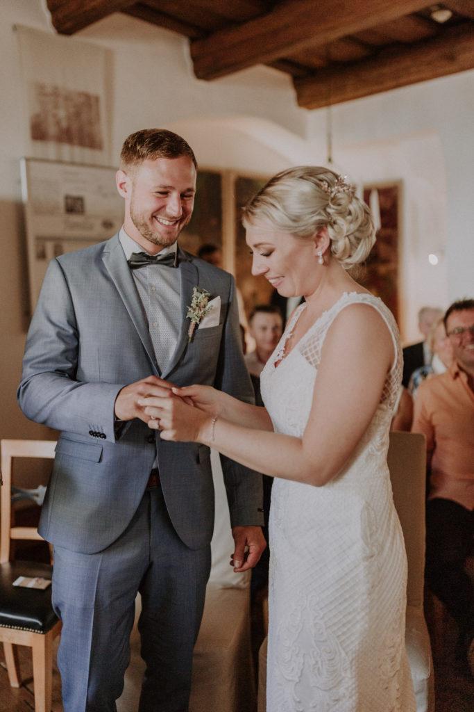 Braut steckt ihrem Bräutigam den Ring an den Finger