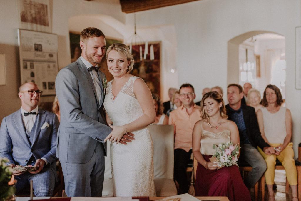 Brautpaar blickt glücklich in die Kamera