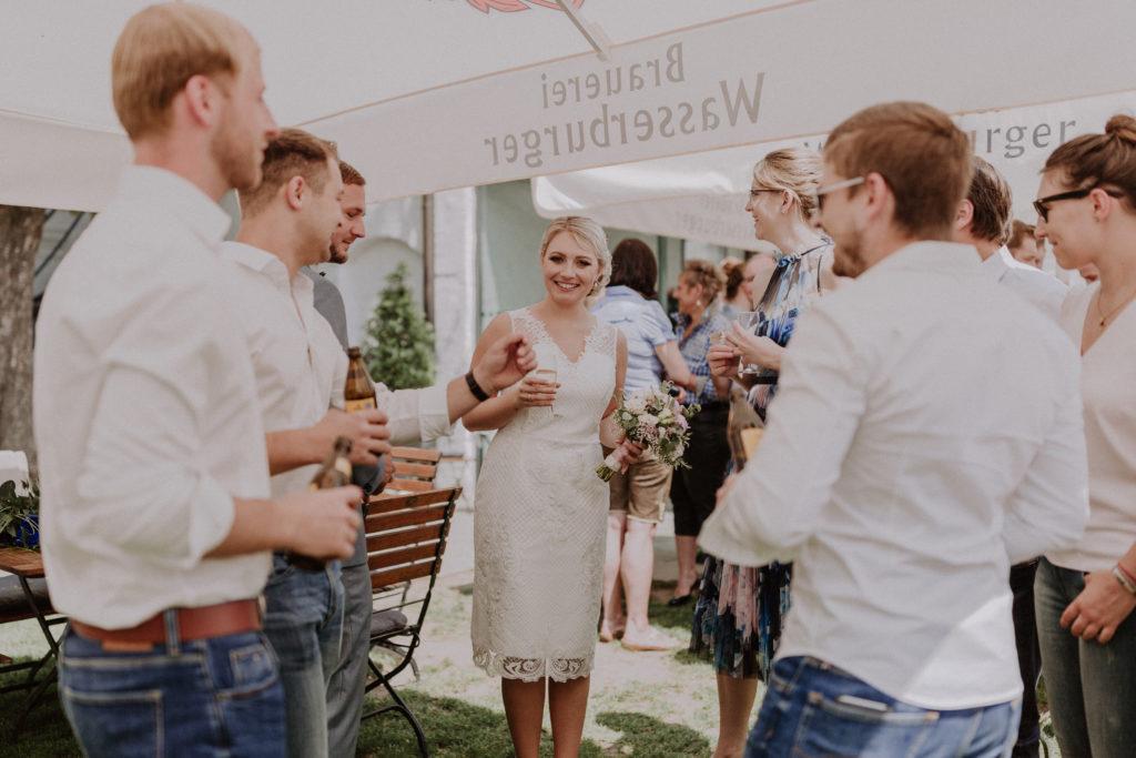 Braut lacht glücklich inmitten von den Hochzeitsgästen