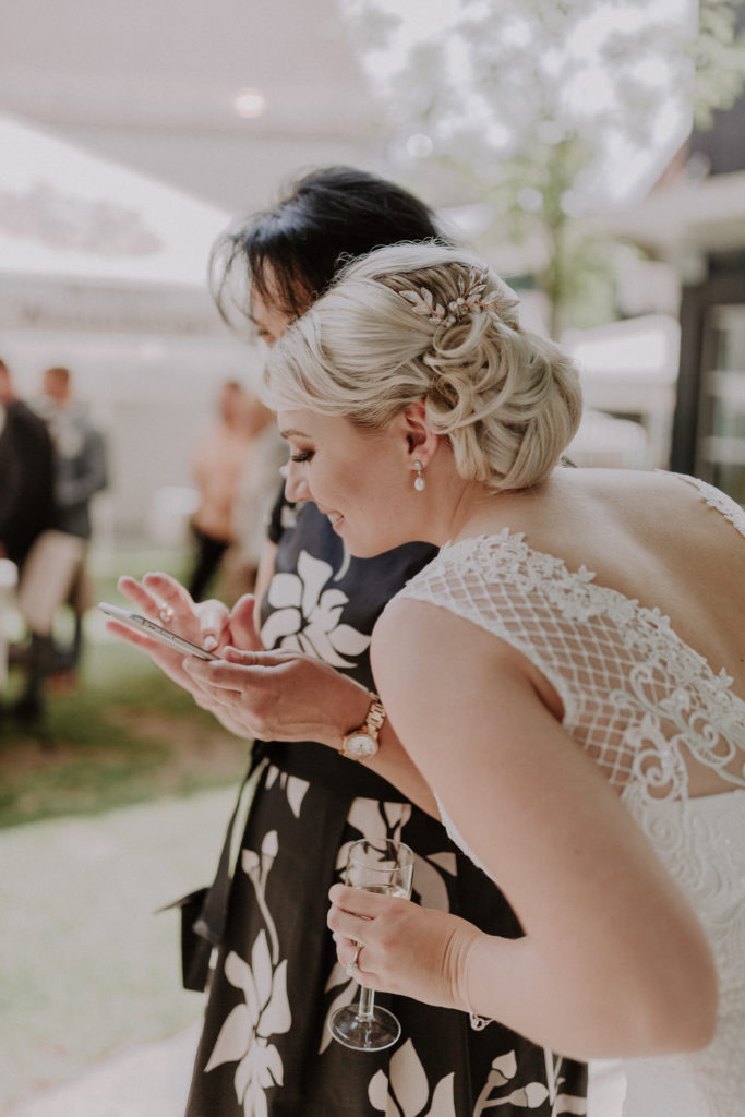 Braut schaut ein von ihr gemachtes Foto auf dem Handy an