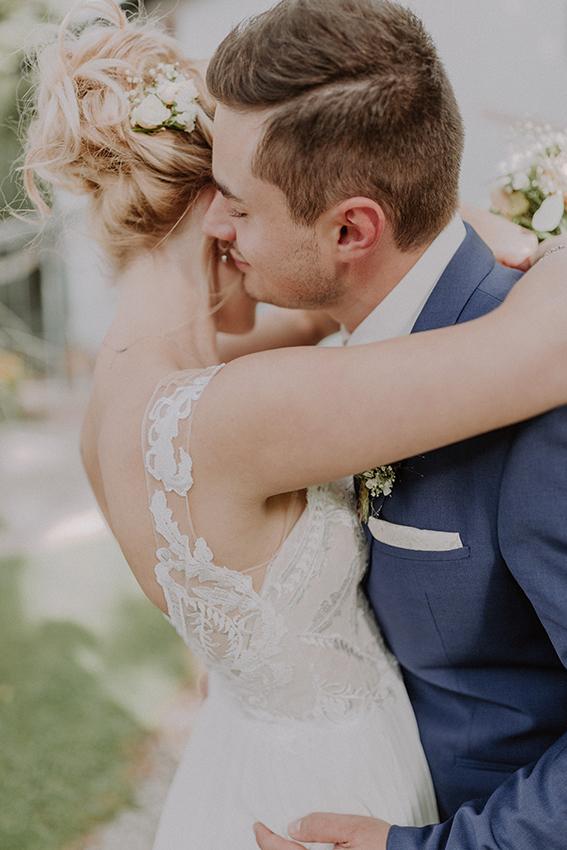 Brautpaar eng umschlungen mit Blick auf die Frisur der Braut