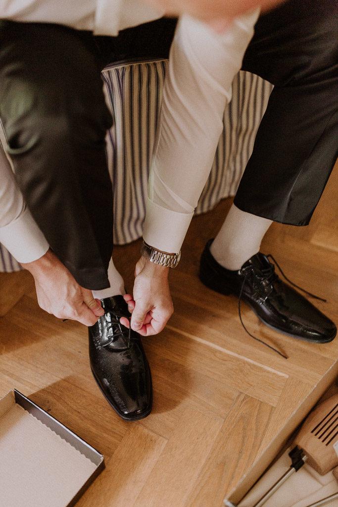 Bräutigam zieht seine Schuhe im Hotelzimmer im Schloss an