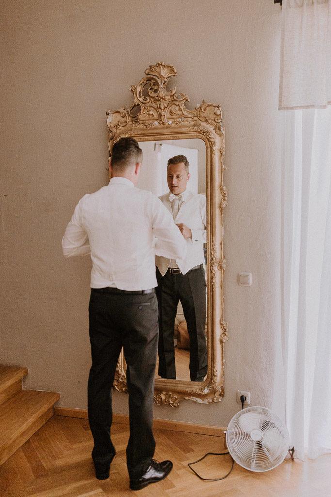 Bräutigam vor Spiegel im Hotelzimmer des Schlosses