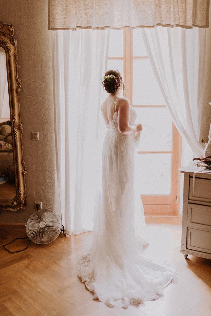 Braut blickt mit ihrem Brautkleid durch das große Fenster des Schlosses