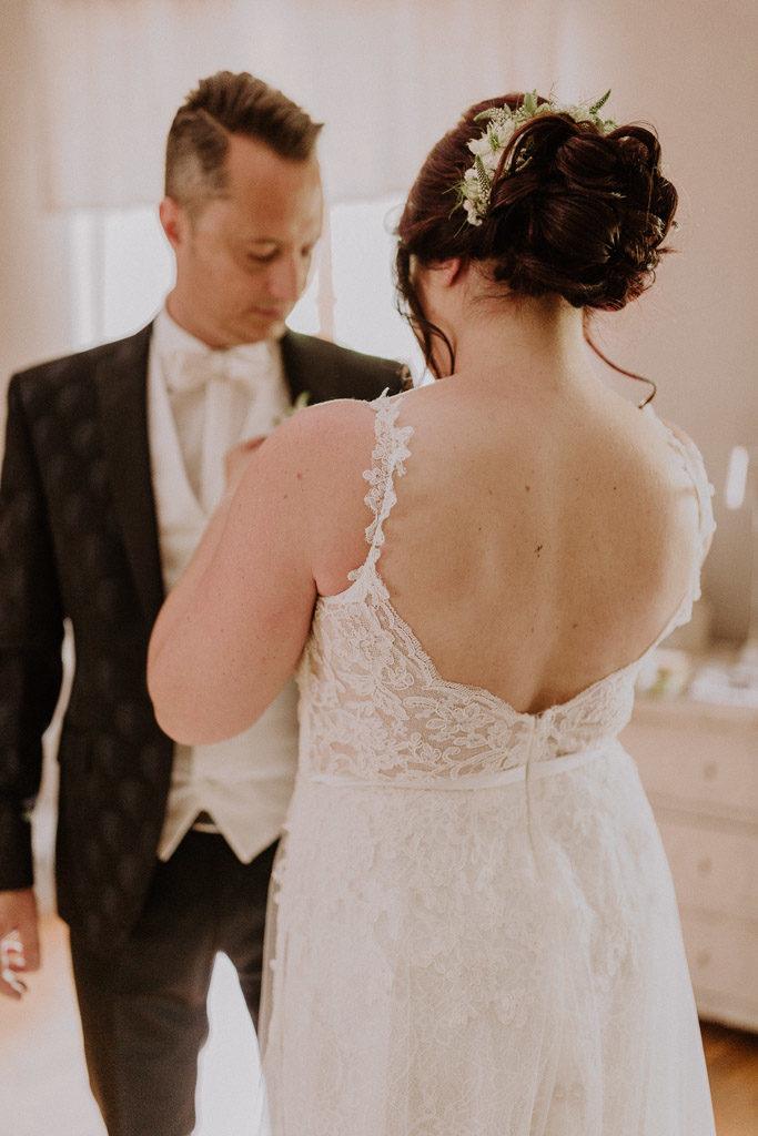 Brautpaar hilft sich gegenseitig im gemeinsamen Zimmer anzukleiden