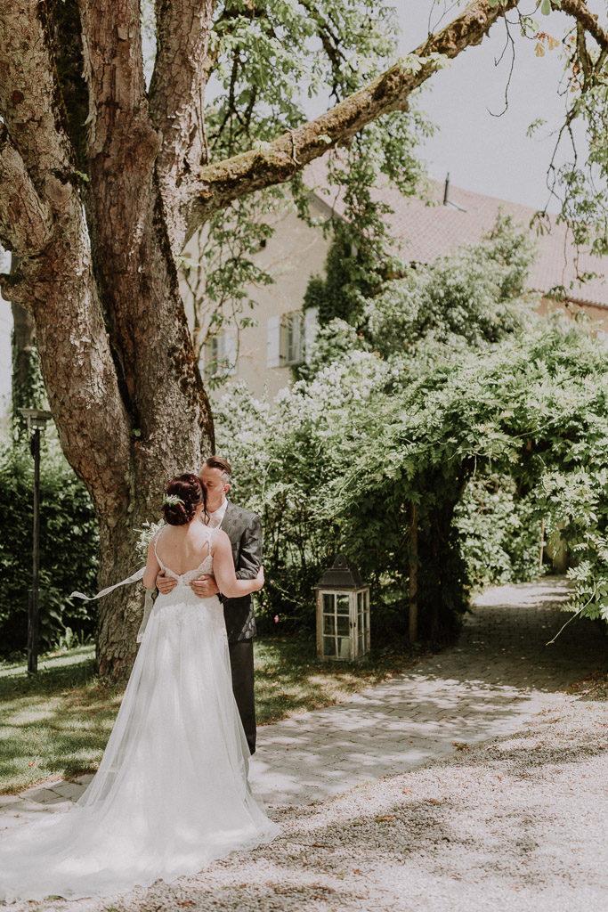 Brautpaar küsst sich im Schlossgarten vor märchenhafter Kulisse