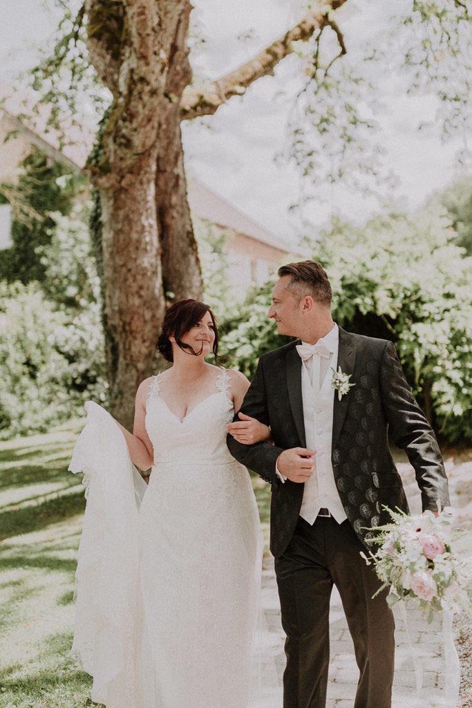 Brautpaar schreitet glücklich und sich anlächelnd im Schlossgarten Amerang entlang