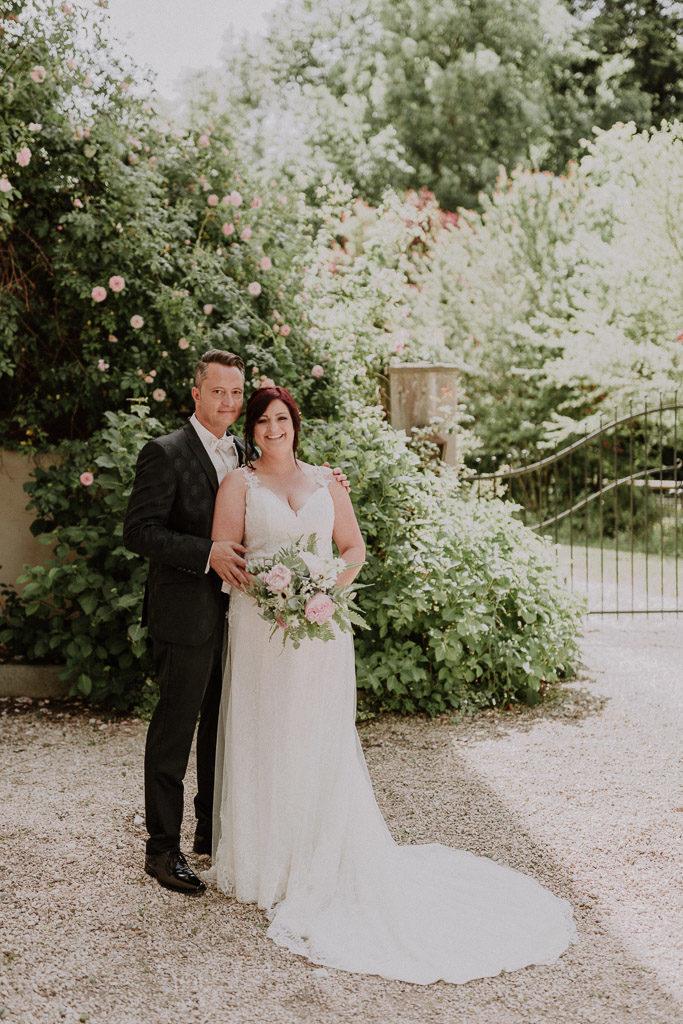 Brautpaar lacht glücklich in die Kamera mit verträumter Kulisse des Schlosses