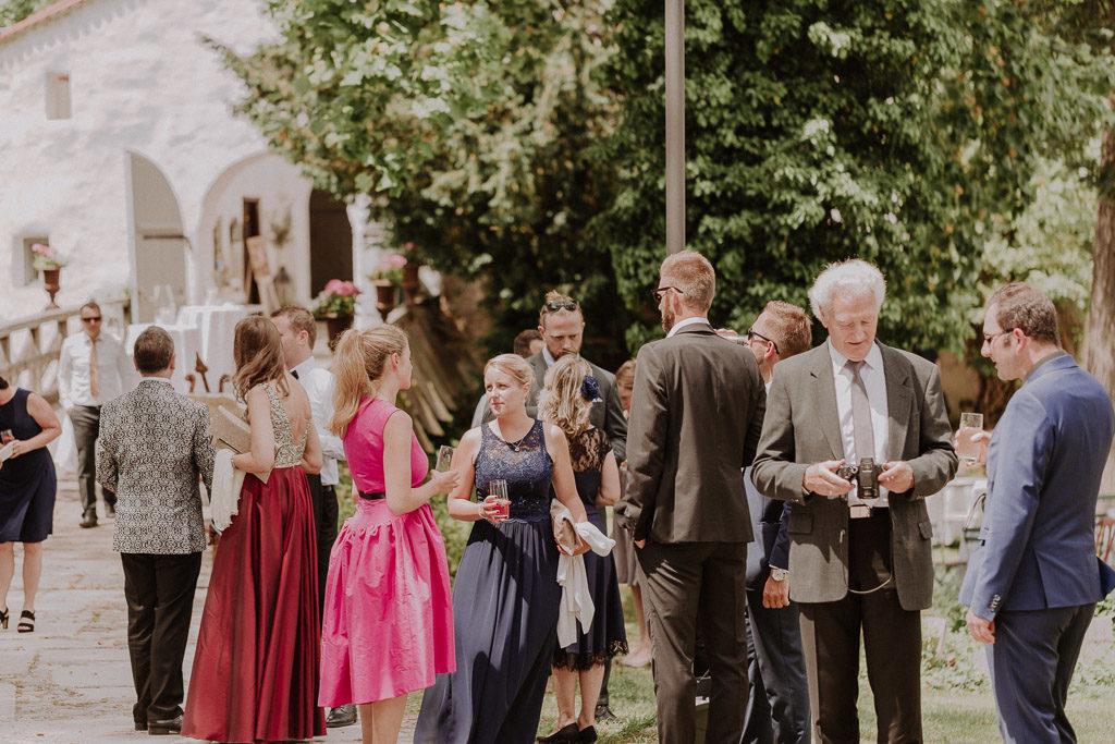 Hochzeitsgäste genießen das Sommerwetter vor der freien Trauung im Schloss Amerang