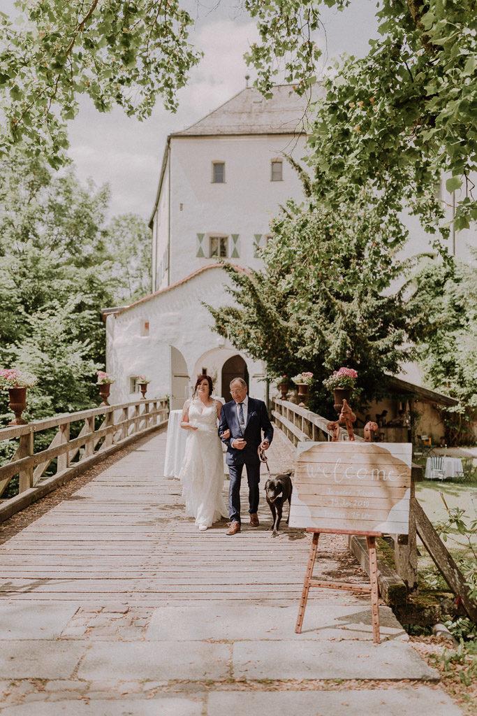 Braut wird von ihrem Vater vor der Kulisse des Schlosses zur Trauung geführt