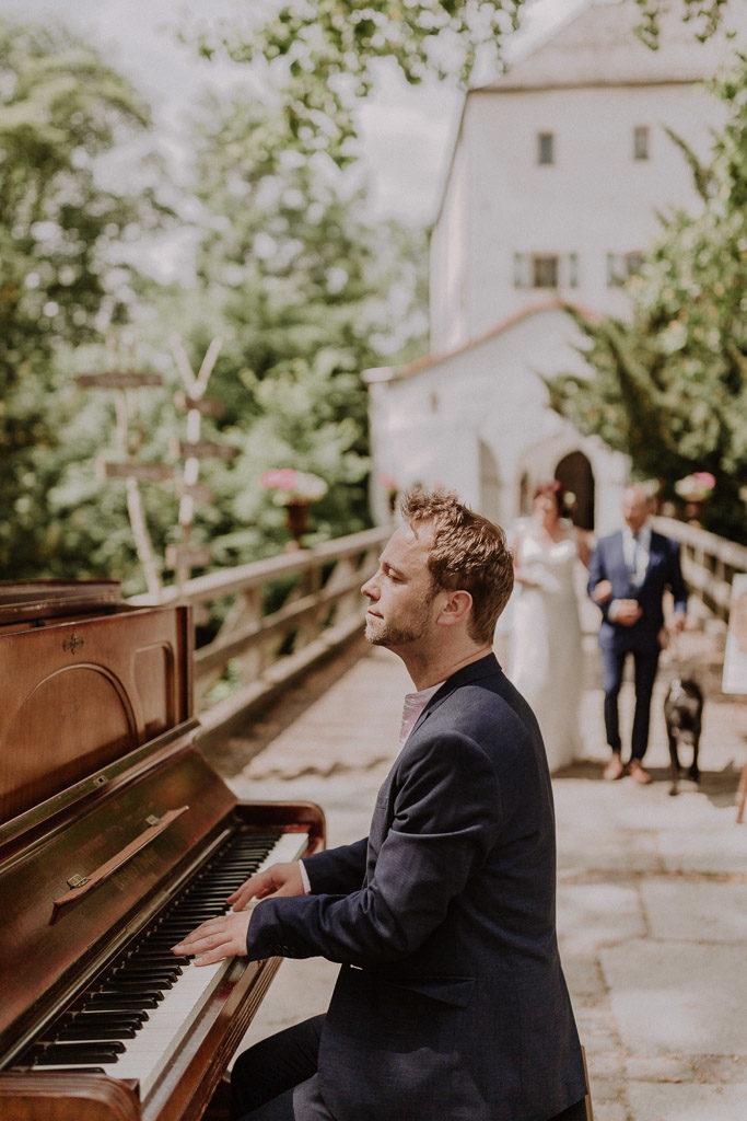 Klavierspieler vor der Kulisse des Schlosses