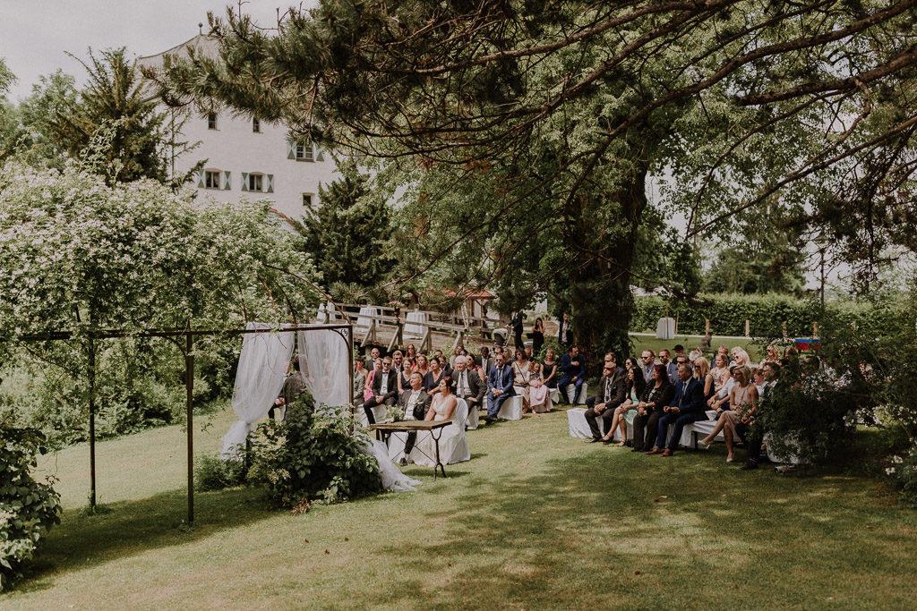 Die freie Trauung mit Hochzeitsgästen im Schlossgarten umgeben von Bäumen und Sträuchern