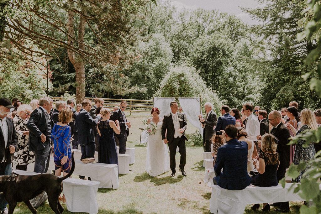 Brautpaar nach der Trauung mit Blick auf die schöne Traukulisse im Schloss