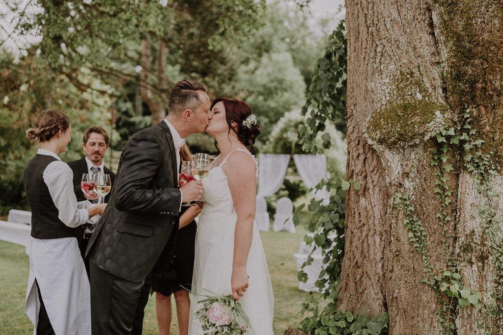 Küssendes Brautpaar zum Sektempfang