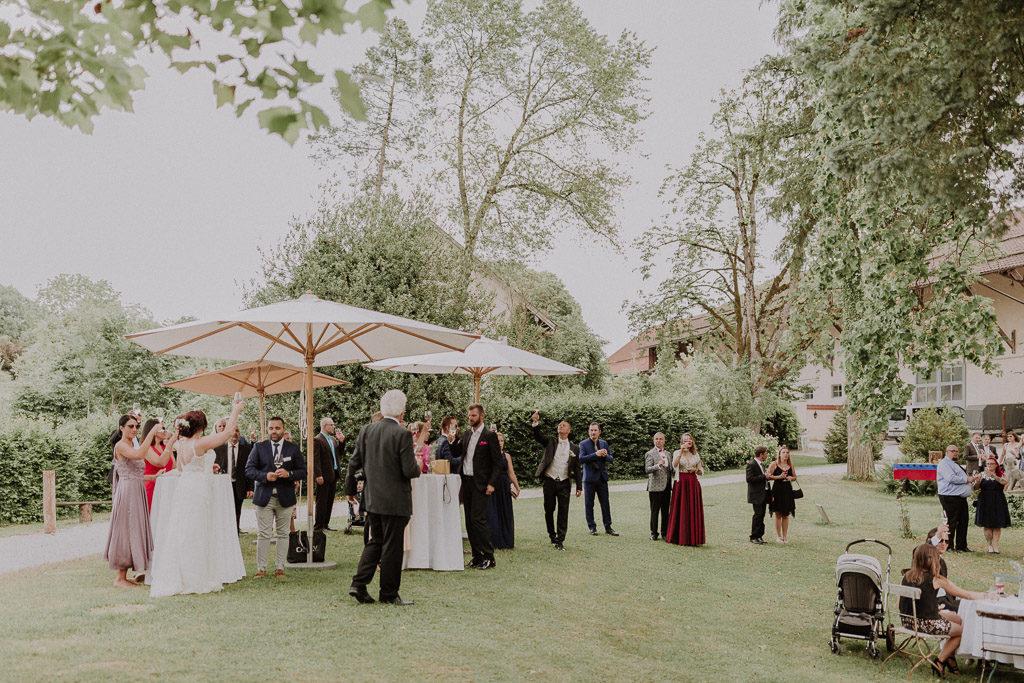 Sich zuprostendes Brautpaar im Schlossgarten